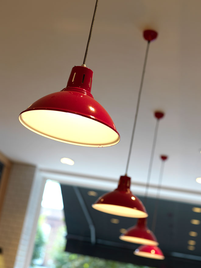 Red pendant lamps light the bakery counter area