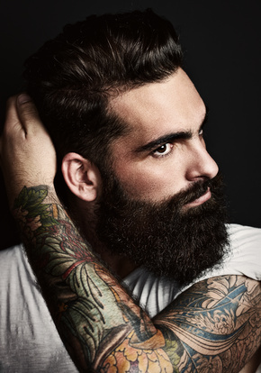 portrait of handsome bearded man with tattoos