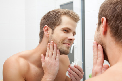 Man looking into the mirror and applying aftershave