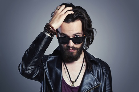 51283611 - young bearded man in a leather jacket. hipster in sunglasses