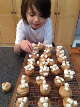 Photo of my daughter placing mini marshmallows on cupcakes.