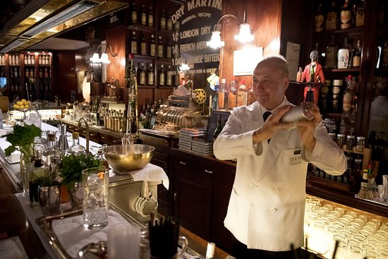 A classic bartender shaking a cocktail behind the wooden bar counter in Dry Martini cocktail bar