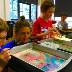Pictured is one of our senior faculty members a few summers ago, Susie Tarnowicz, overseeing a couple of students bringing their math to life through art.
