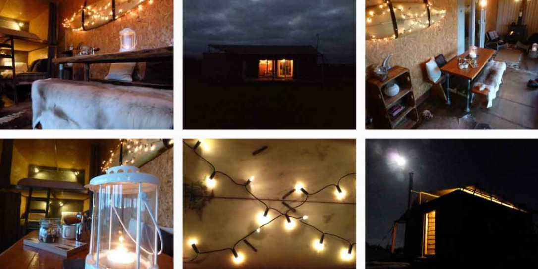 fairy lights, lanterns, surfboard and the cosy glow of rusty the tin tent converted shipping container in the moonlight at barefoot glamping Cornwall