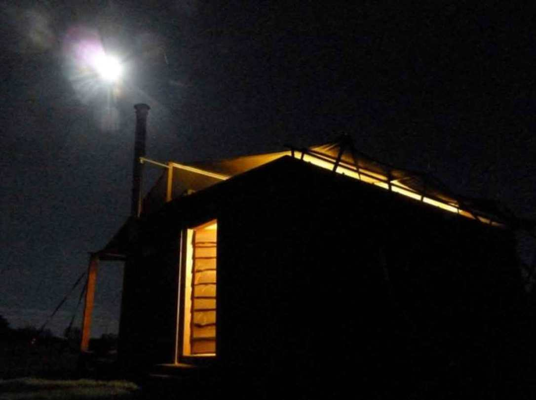 outside rusty the tin tent converted shipping container at night with the moon shining and a cosy glow at barefoot glamping Cornwall