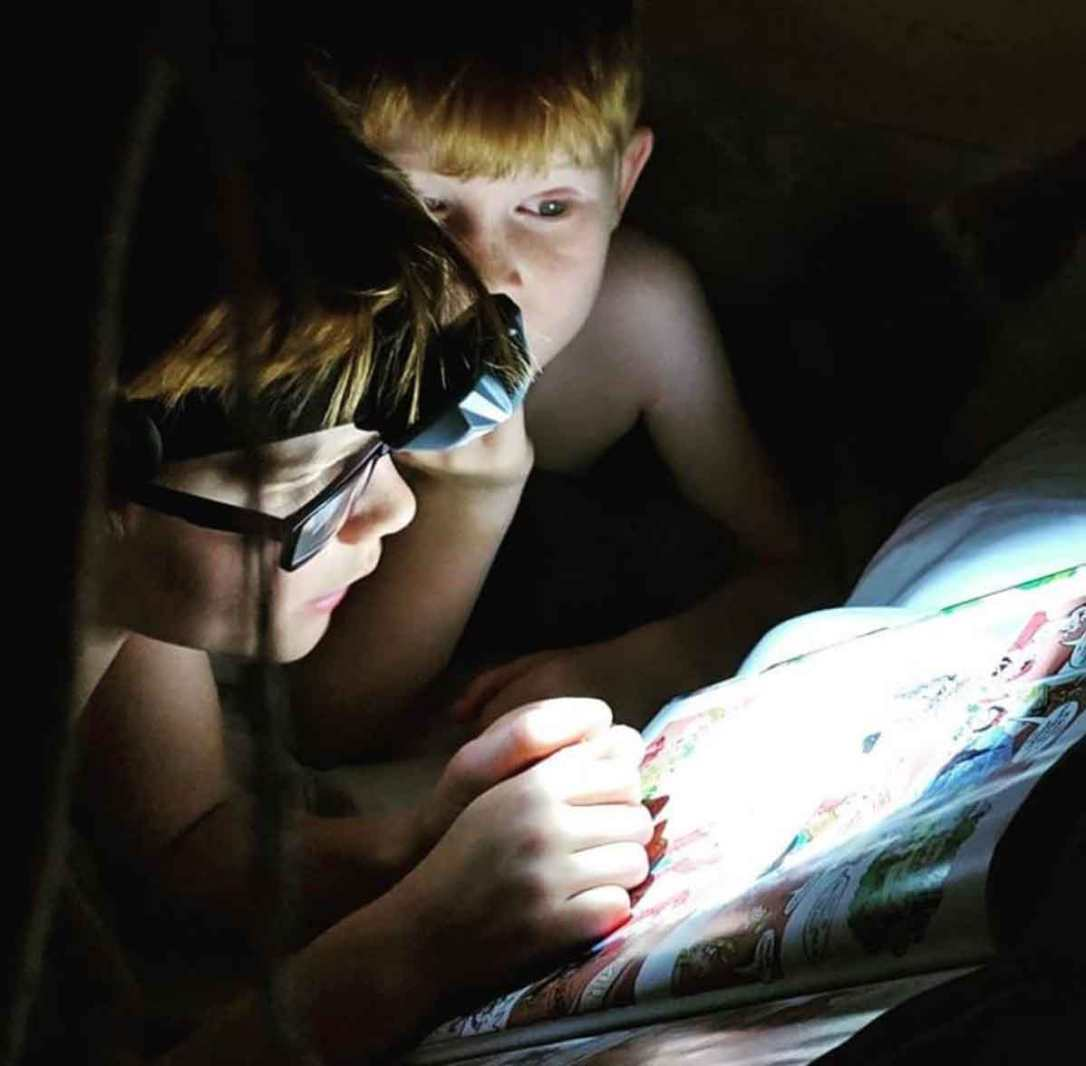 boys with head torches reading in bed in woody the safari tent