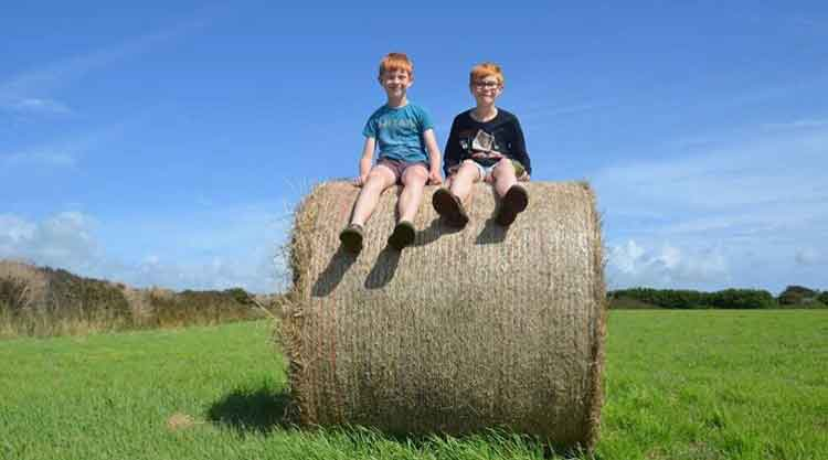 boys sitting on top of a hay bale in the Glamping meadow