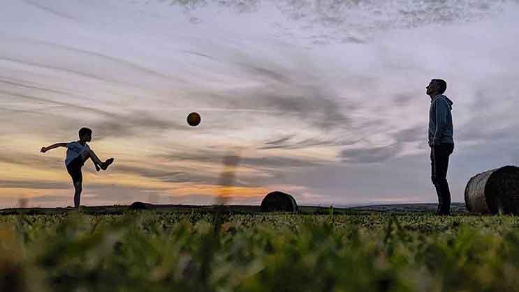 father and son playing football in the meadow with a sunset and hay bales