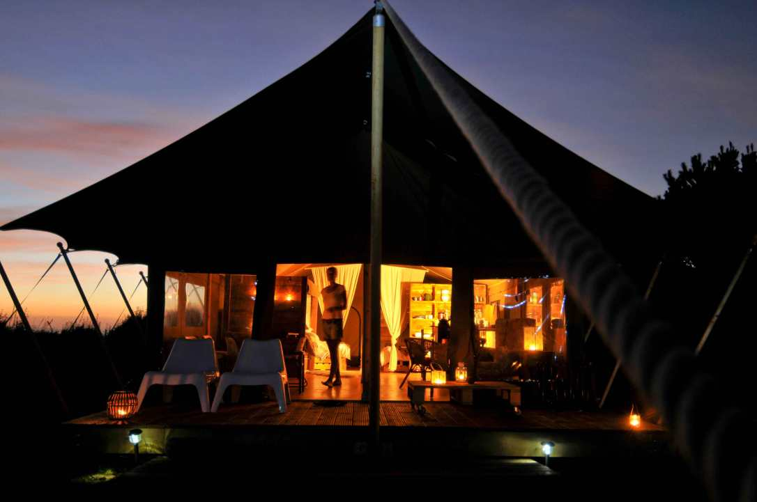 Hobie, a safari tent at night with lanterns and sunset glow
