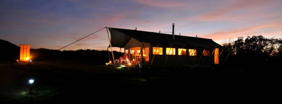 Hobie safari tent at night with a sunset a lantern glow