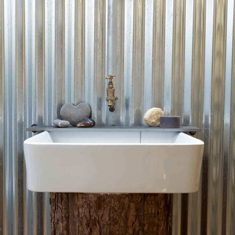 the wriggly tin clad ensuite wash room with basin on a tree stump