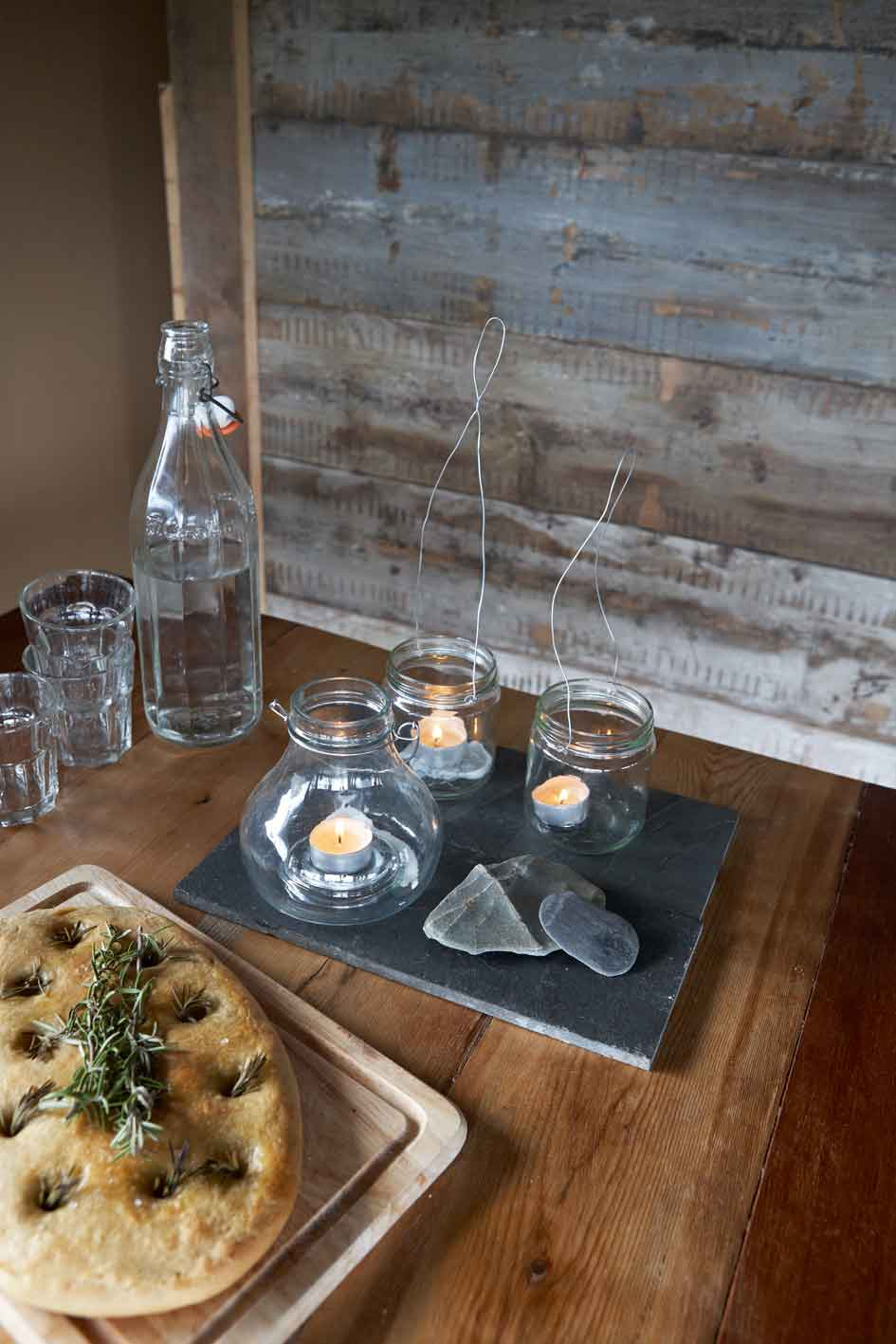 focaccia bread on the table next to water bottle and tea light lanterns