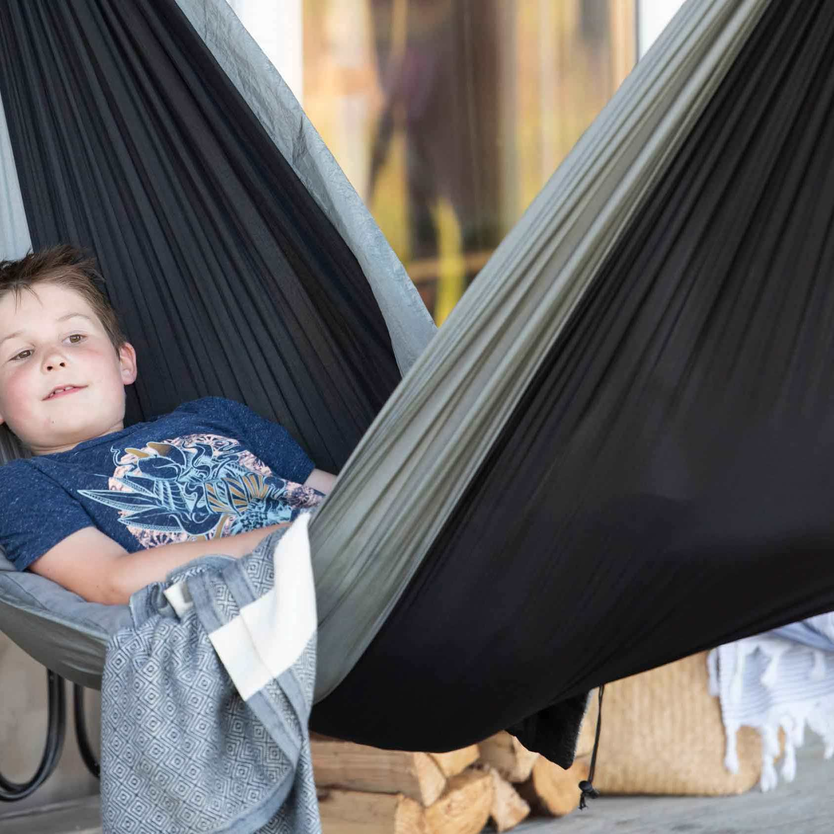 boy relaxing in a hammock outside rusty the tin tent