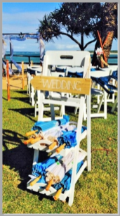 Beach stand with parasols & wedding sign.