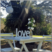 Square signing table with love sign & flowers.