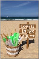 Wedding sign and basket of parasols.