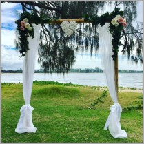 Bamboo wedding arbour styled with white chiffon, green ivy, pink & white faux flowers & white wicker love heart. Mooloolaba Spit, Sunshine Coast.