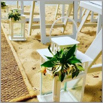 White lanterns styled with fresh greenery.