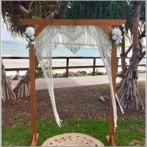 Timber wedding arch styled with macrame hanging and white faux flowers. Happy Valley, Caloundra. Sunshine Coast
