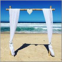 Bamboo wedding arbour styled with lace curtains and love heart. Small white posies with white sashes for ties. Wedding ceremony Buddina Beach, Sunshine Coast.