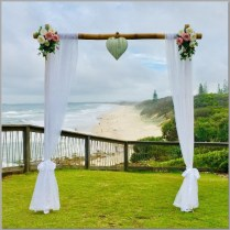 Bamboo wedding arbour styled with white curtains, pink and white faux flowers and love heart. Pt Arkwright, Sunshine Coast.