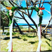 Timber wedding arbour styled with white curtains, green ivy and pink & cream peony faux flowers. Kawana Surf Club, Sunshine Coast.