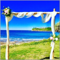 Bamboo wedding arch styled with white chiffon & native faux flowers and greenery. Location - Sir Leslie Wilson Park, Caloundra.