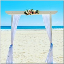 White timber wedding arch styled with white chiffon curtains and faux pink and white flowers and greenery. Mooloolaba Beach.