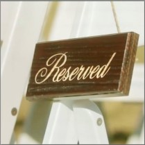 Wooden reserve signs for front row wedding chairs.