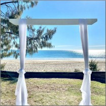 White timber wedding arch styled with white chiffon curtains. Noosa.