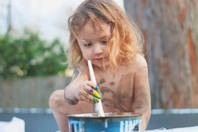 Toddler dips brush into paint