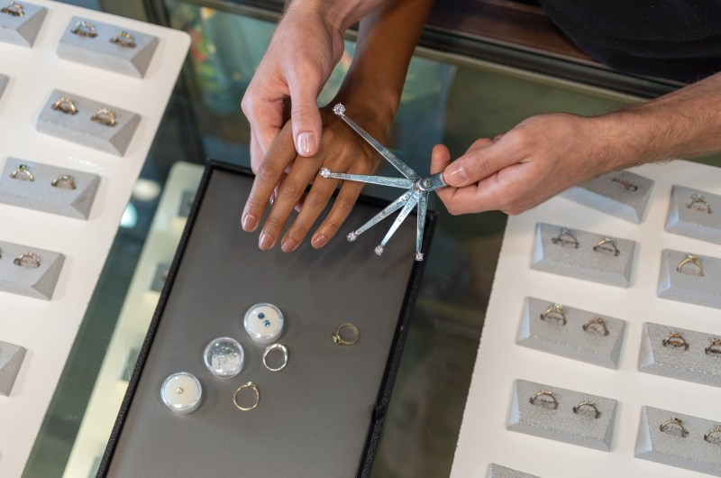 Photograph of two hands trying different ring designs