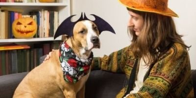 Showing a pet owner and her dog with costumes on.