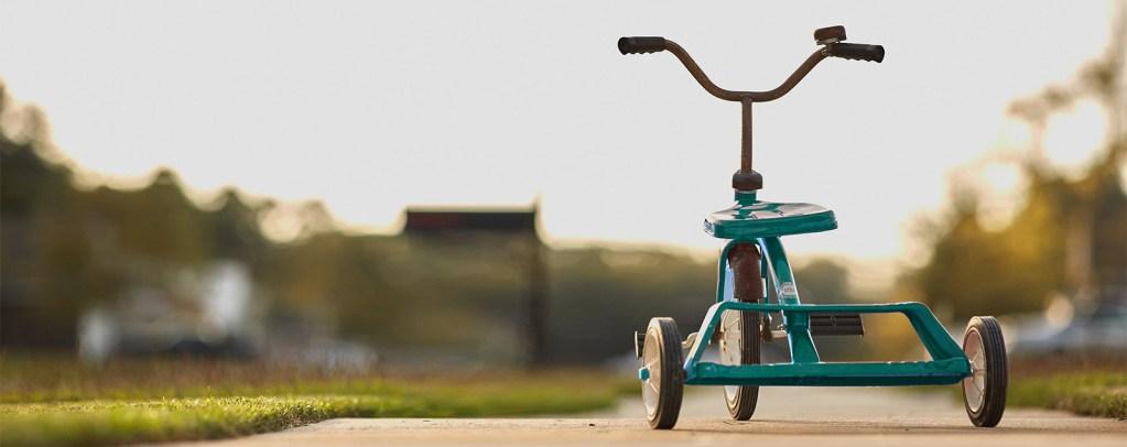 En ensom grønn trehjulssykkel på en stille vei