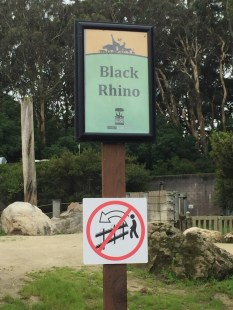 """At the zoo's rhino enclosure. I think the bottom sign means """"Don't be a complete dick""""."""