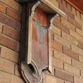 Gothic style bat house on brick wall