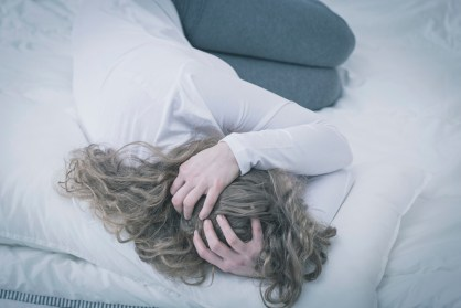 Troubled young woman curled up in bed