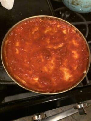 spread sauce to edge of pan - homemade bar pizza