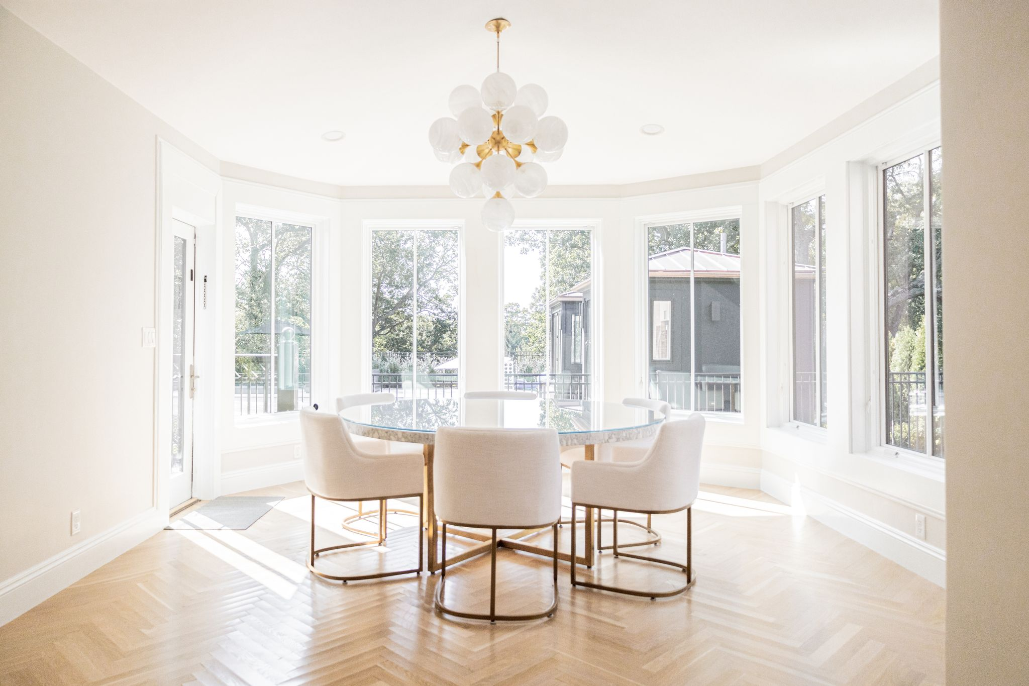 Picture of airy bright dining room with hardwood floors and white chairs.