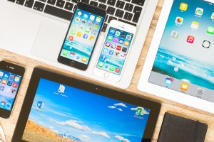 Brand new Apple iPhones 6 and 5S sit on a Macbook keyboard surrounded by iPad tablets and various other Apple devices.