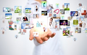 Virtual meeting concept. A large number of screen avatars hover above an open hand.