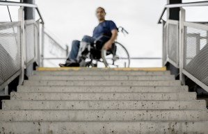 A man in a wheelchair stares down a flight of steps that are inaccessible.