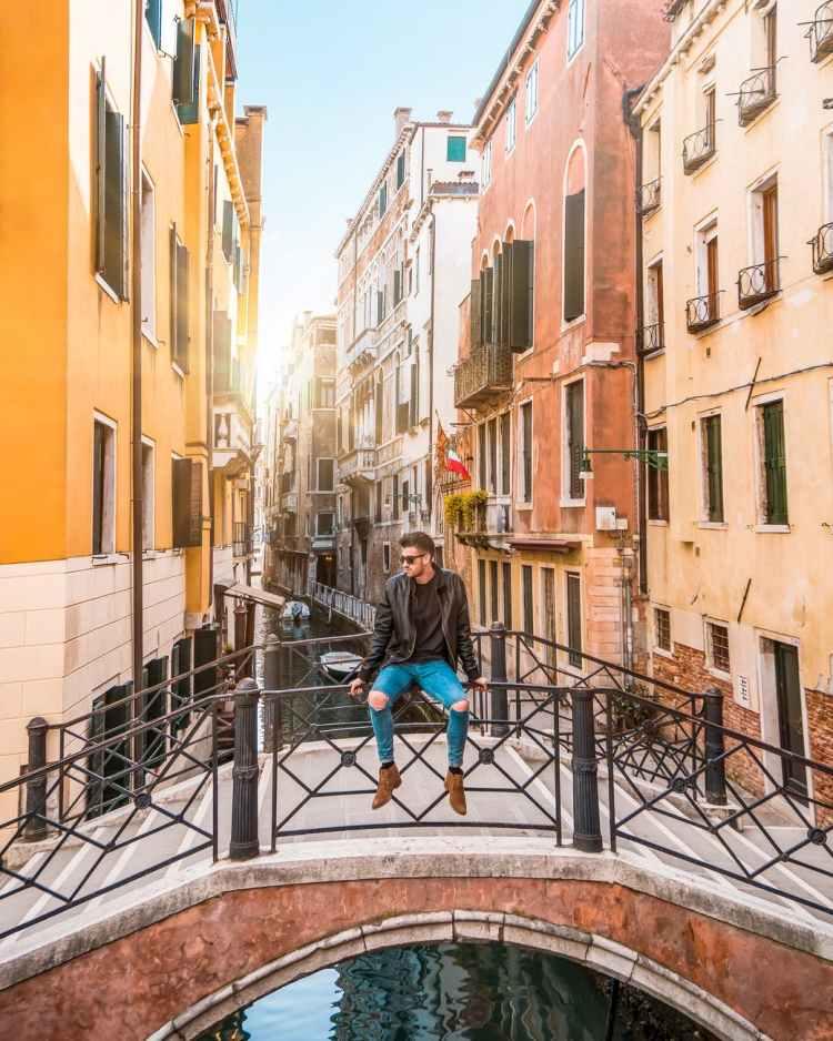 man sitting on bridge railings