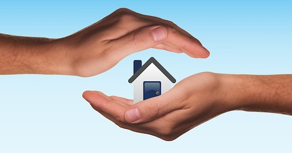 Hands protecting house representing property insurance