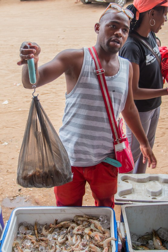 A local seller weighs prawns in Ponta do Ouro, Mozambique