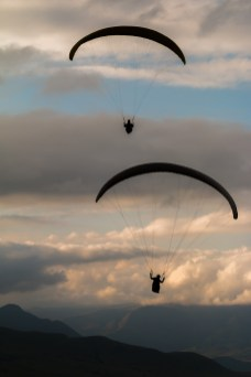 Two paragliders silhouetted against a cloudy sky at sunset