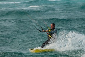 A Kite Surfer kicks up spray behind his board