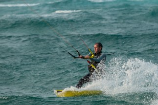A Kite Surfer kicks up spray behind his board