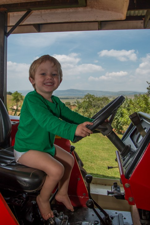 A young boy pretending to drive a tractor