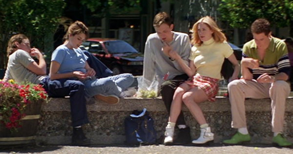 Scream (1996). Sidney is sitting on a low wall outside of the high school with her group of friends, including the preppy Randy and her boyfriend Stu. Sidney is leaning on the leg of her boyfriend Billy, who is lay back watching his friends.